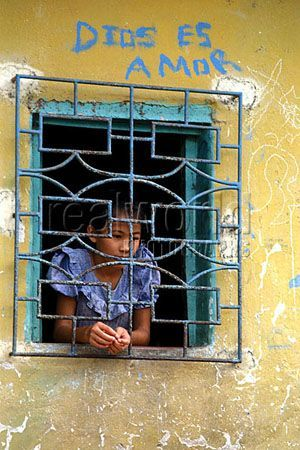 A young girl stares out into the world from behind bars on windows of her home in San Salvador, El Salvador in Central America. The graffiti above reads 'God is Love'.