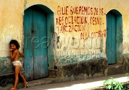 A young girl stands next to slogan painted wall in the rebel held area of San Gerardo near San Miguel, El Salvador, Central America.