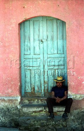 A Guatemalan man watches the world go by in a colorful doorway in Solola, Guatemala. Central America. Gary Moore photo.