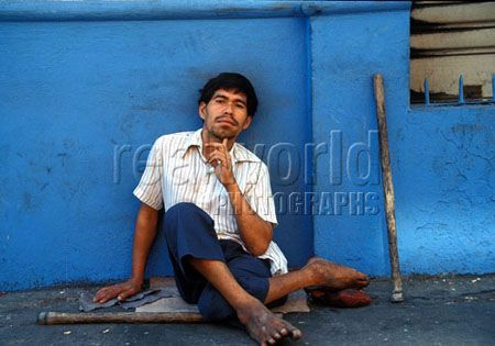 A crippled man contemplates his existence on a dirty sidewalk in San Salvador, El Salvador.