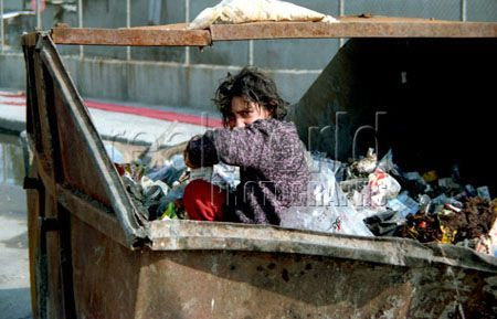 A young girl searches for food in a garbage dumpster in Istanbul, Turkey.