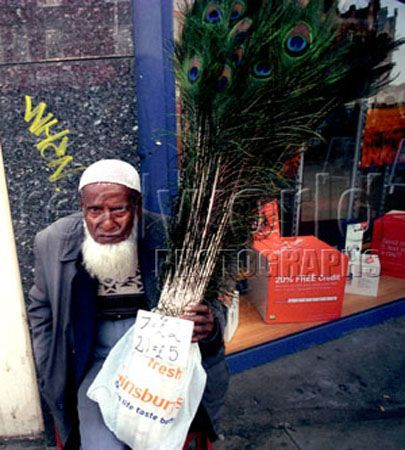 A Muslim Man sells peacock feathers in Camden Town, North London, UK. Gary Moore photo.
