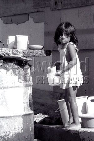 A young girl washes dishes at a makeshift sink in San Salvador, El Salvador, Central America. Gary Moore photo.