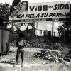 A semi-naked barefoot boy stares curiously at the photographer while a man collects garbage under a sign warning of the dangers of AIDS on the outskirts of San Salvador, El Salvador, Central America.