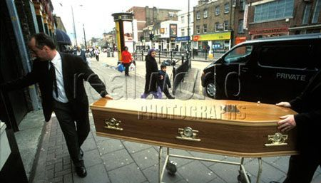 Two pallbearers wheel a casket onto Bethnel Green high street, East London. A sign that life goes on when we are gone.