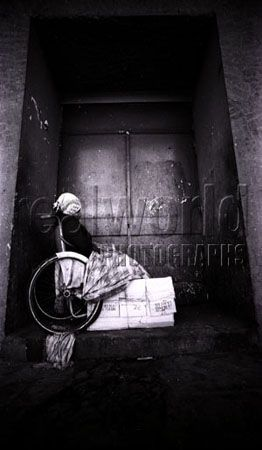 A wheelchair bound woman sits in utter desperation in a filthy doorway in the center of San Salvador, El Salvador, Central America.