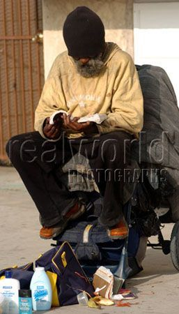 A homeless man uses a baby carrige as a seat while indulging in a book.  Venice beach, Santa Monica, California. USA.