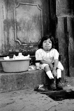 A young disabled  girl sells bags of water in a doorway in San Salvador, El Salvador, Central America.