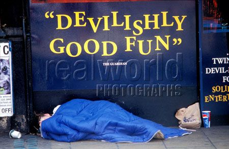 A homeless man sleeps under an advertisement for a play in London�s west end. UK.