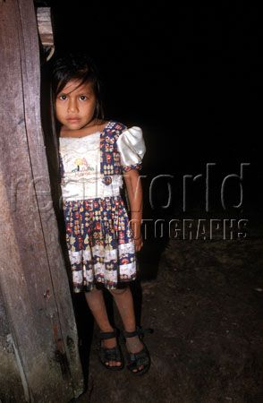 A young girl in her Sunday dress leans against the entrance way to her home near in the Amazon jungle border town of Leticia, Colombia, South America.
