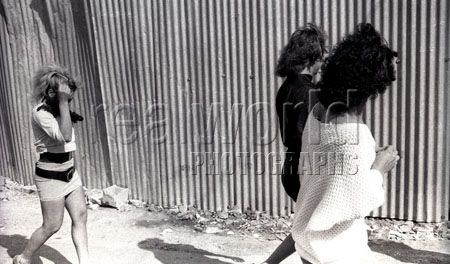 Three transvestites hide their faces while out walking in downtown San Salvador, El Salvador, Central America.