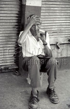 An old beggar tries his luck with a wooden flute in a back alley in San Salvador, El Salvador, Central America.