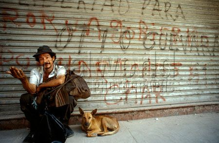 A homeless man and his dog use a sidewalk to beg for hand-outs in Guatemala City, Guatemala, Central America.