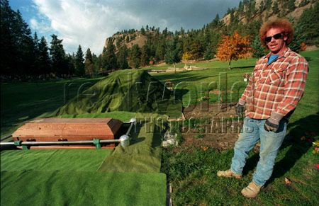 A gravedigger with a freshly dug grave and coffin in Kelowna, British Columbia, Canada. All in a days work. Maybe 6 feet isn�t that far down.