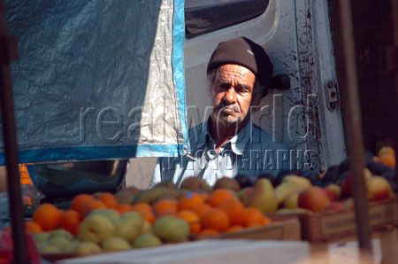 A fruit and vegetable vendor in Whitechapel, east London takes advantage of a stream of sunshine to sit back and steal a moment to himself.