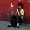 A young shoeshine boy perches under an advertisement for Gallo beer in San Salvador, El Salvador, Central America.