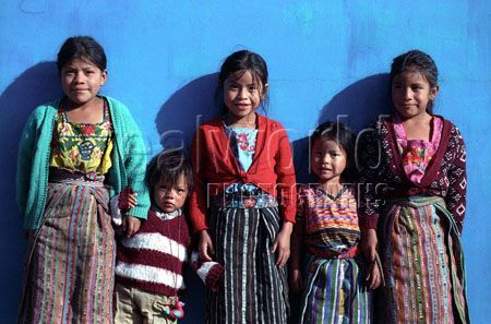 Young children in Guatemala in colorful fabrics pose against a colorful tomb while visiting lost relatives at a cemetery in Solola, Guatemala, Central America.