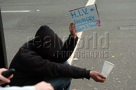A homeless man uses a hand-made sign and a blunt message while begging in downtown Vancouver, British Columbia, Canada.