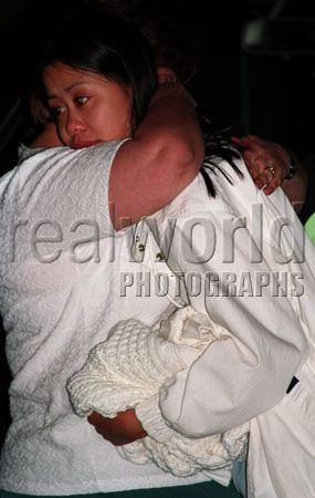 Mimi Tran, sister of 8 year old Mindy Tran gets a hug from a neighbor shortly after Mindy went missing. She was later found murdered and buried in a park near her home. No one has ever been convicted for the crime.