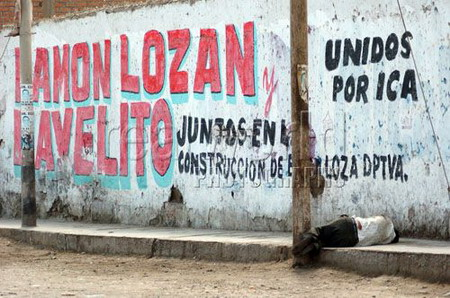 A drunk man with no shoes lays passed out under a wall painted with political graffitti in Pisco, Peru, South America.