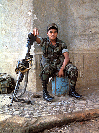 A Salvadorean soldier uses his weapon to lean on on a street corner in Usulutan, El Salvador, Central America.